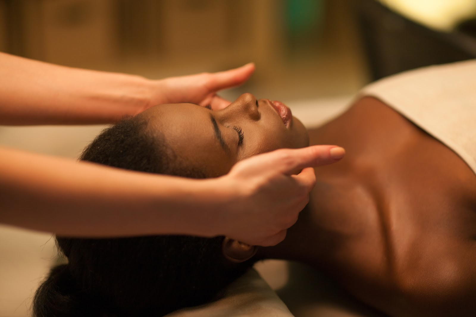 Young African woman having her face massaged.